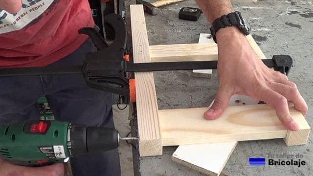 perforando la madera para hacer las patas traseras de la silla de madera para niños con tornillos
