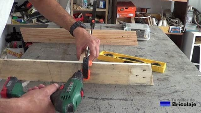 sujetando las piezas que formarán la silla de terraza