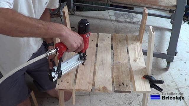 clavando los listones de madera a las patas delanteras de la silla de terraza