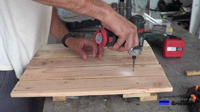 sujetando la madera de palets para hacer las sillas de terraza