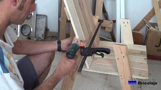 atornillando el respaldar de la silla de terraza de palets