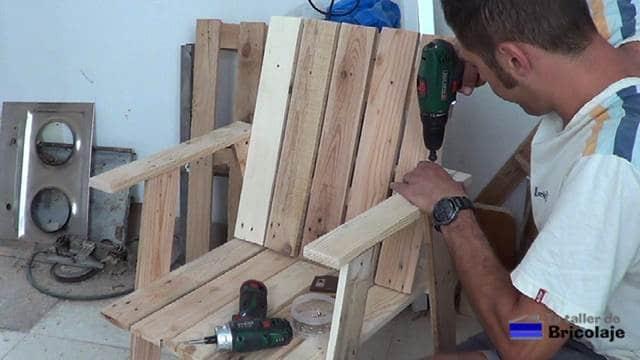 perforando para sujetar el apoyabrazos en las sillas de palet de terraza