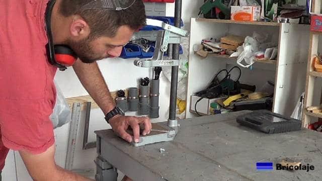 sujetando el soporte para el taladro a la mesa de trabajo