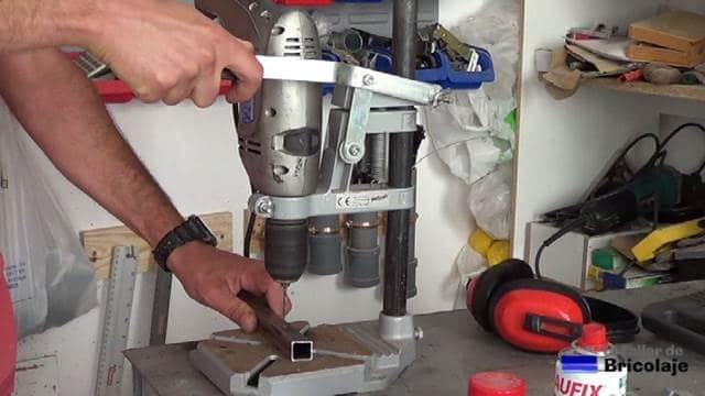 perforando un trozo de cuadradillo de hierro con el soporte