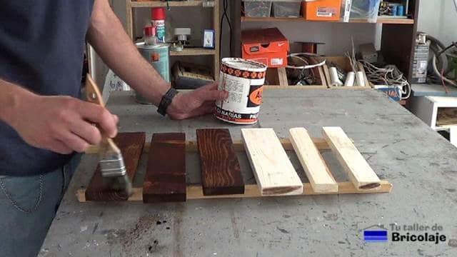 aplicando tinte a la madera de palet