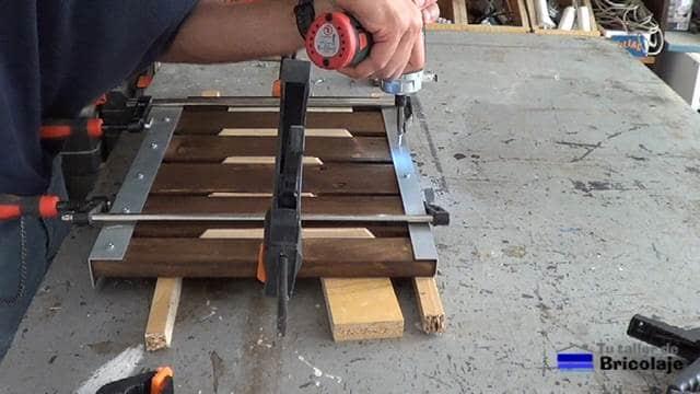 atornillando el ángulo superior a la madera de palet
