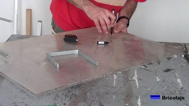 marcando en el policarbonato para colocar un trozo de chapa de aluminio