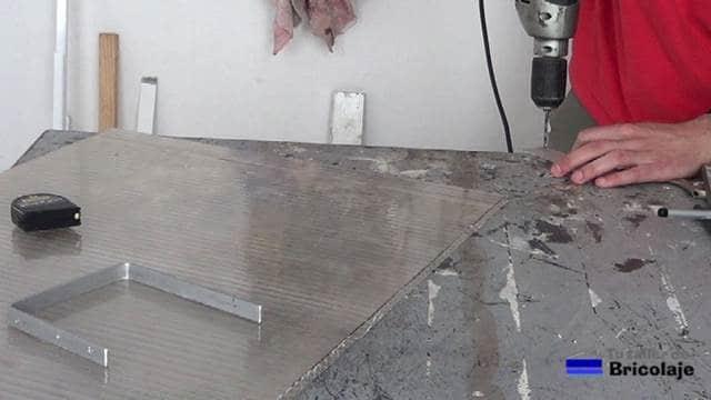 perforando la chapa con un taladro para sujetarlo a la chapa de policarbonato
