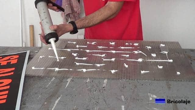 aplicando silicona para pegar el cartel a la plancha de policarbonato