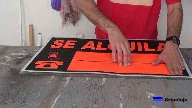 pegando el cartel en la plancha de policarbonato