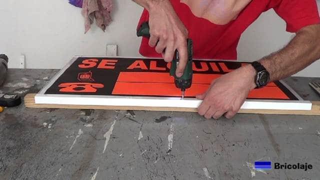 atornillando el ángulo a la plancha de policarbonato