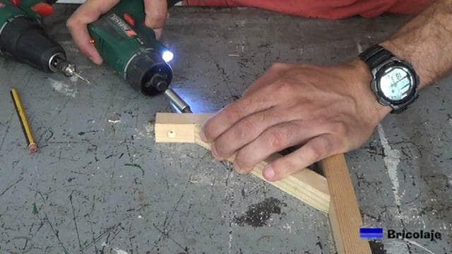 atornillando las piezas para hacer el soporte