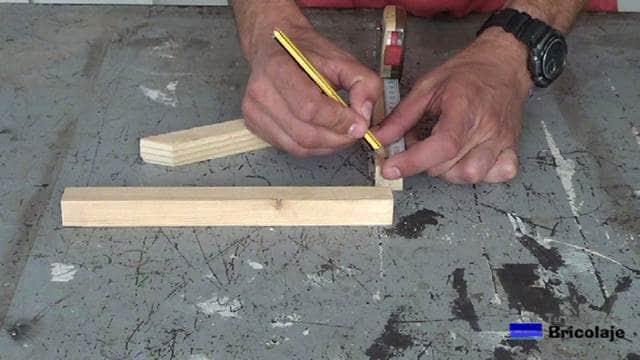 marcando el lugar donde perforar la madera para sujetar el soporte a la pared