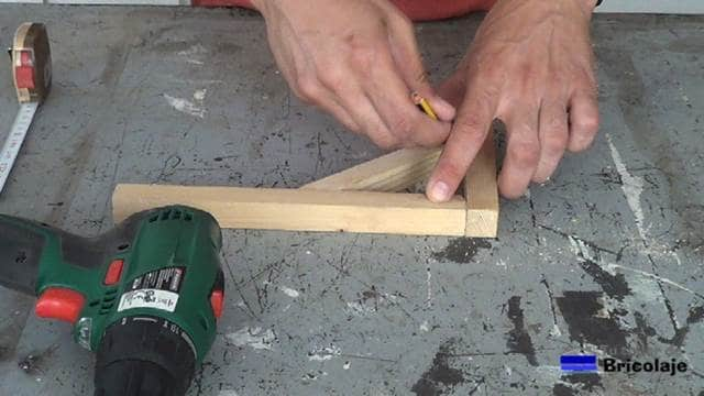 marcando el lugar donde coincide el soporte central con los otros dos listones de madera