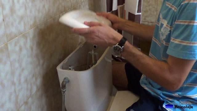 retirando la tapa del tanque para acceder a la válvula de llenado para inodoros