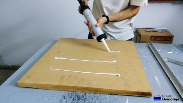 echando silicona para pegar la chapa de aluminio