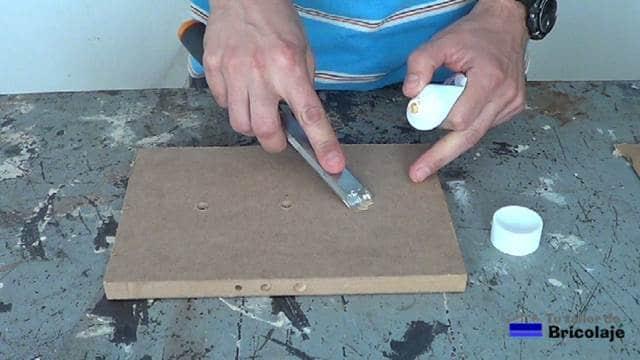 tapando el agujero en la madera con masilla al agua