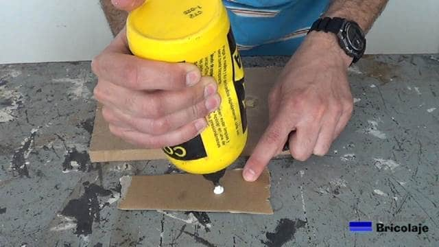 aplicando cola sobre un trozo de cartón para realizar la mezcla