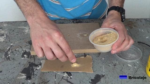añadiendo serrín en polvo a la cola para crear la masilla casera
