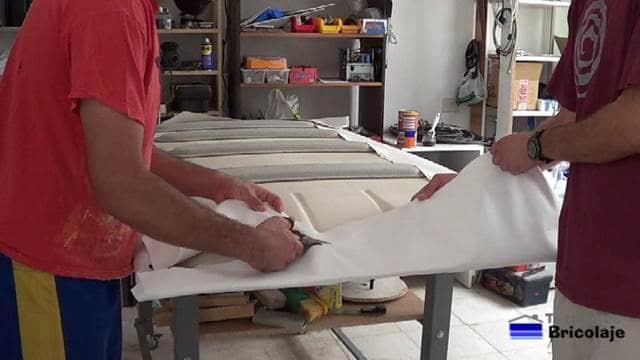 cortando el excedente de tapizado para el techo del coche