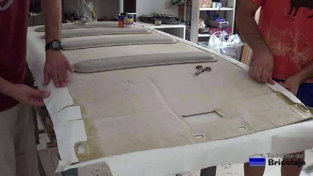 estirando el tapizado del techo del coche
