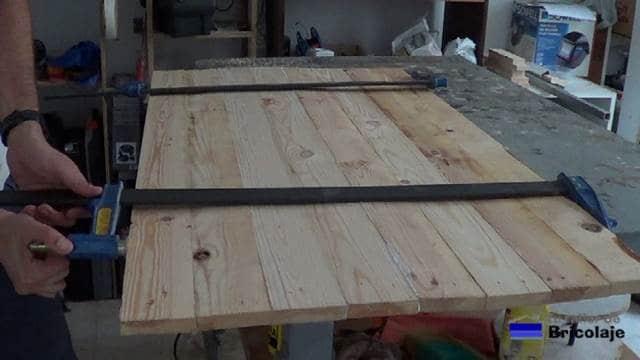 sujetando los listones de madera con sargentos para formar el tablero