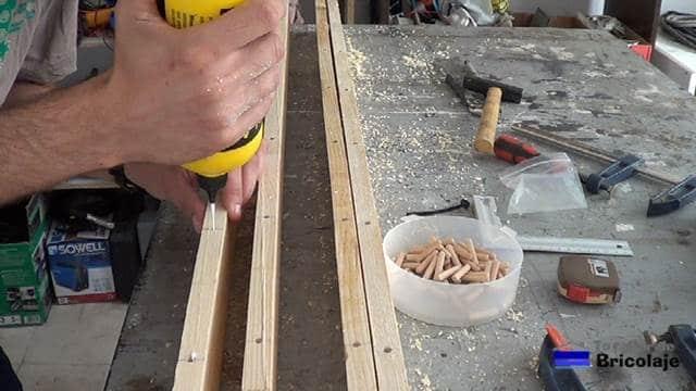 echando cola en los agujeros para pegar los tarugos o espigas