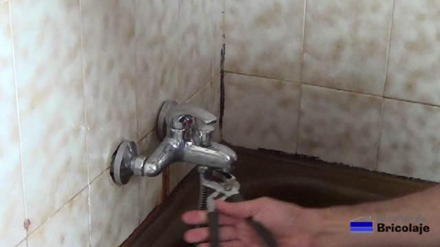 aflojando el flexo o manguera de la grifería de la ducha con la mordaza
