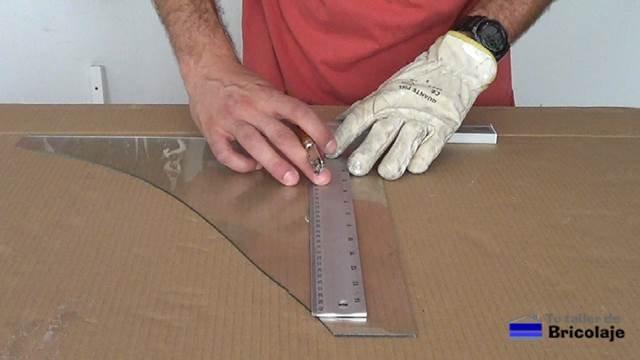 colocando la escuadra sobre el cristal para realizar un corte recto