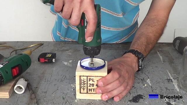 sujetando mediante tornillos la tapa a la base de la lámpara
