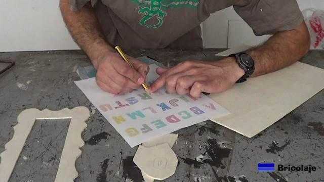 copiando las letras en la madera con el papel de carboncillo