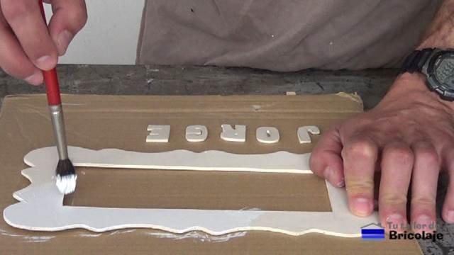 pintando el marco de marquetería para hacer el cartel con el nombre del niño