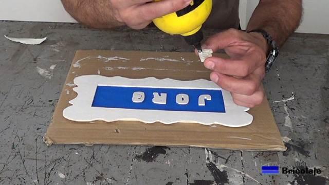 pegando con cola las letras en el cartel