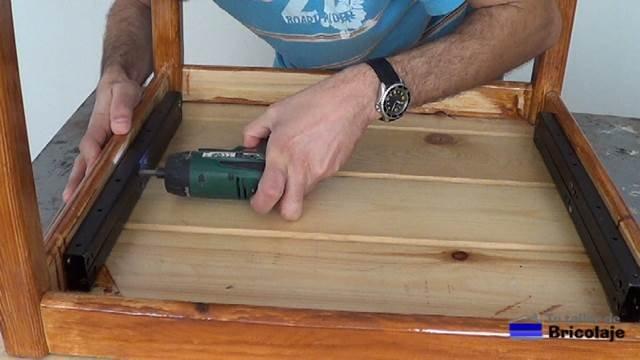 sujetando con tornillos el sistema de elevación al largero de la mesa