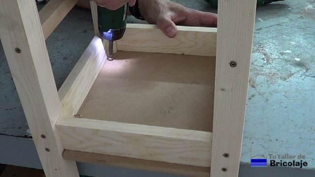 sujetando el asiento a la estructura de la silla con tornillos