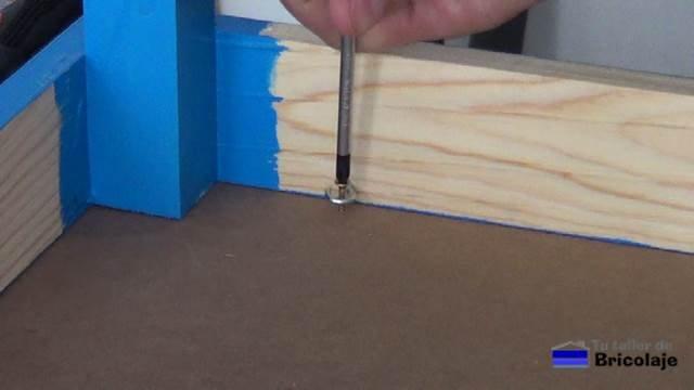 sujetando la cubierta a la estructura de la mesa mediante tornillos y alcayatas redondas