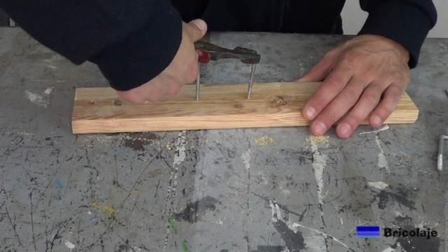 usando unos alicates para colocar las alcayatas en la madera de palets para colgar las brochas y rodillos