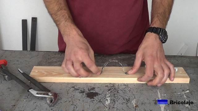 presentando la cinta metálica perforada sobre la base de madera para hacer el organizador