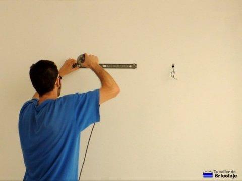 atornillando el soporte del fluorescente a la pared
