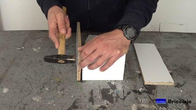 sujetando las piezas de madera con tachas o clavos