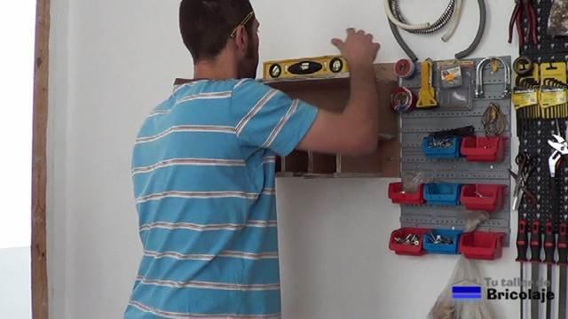 presentando en la pared el lugar donde colocar el mueble organizador de taladros y sus accesorios