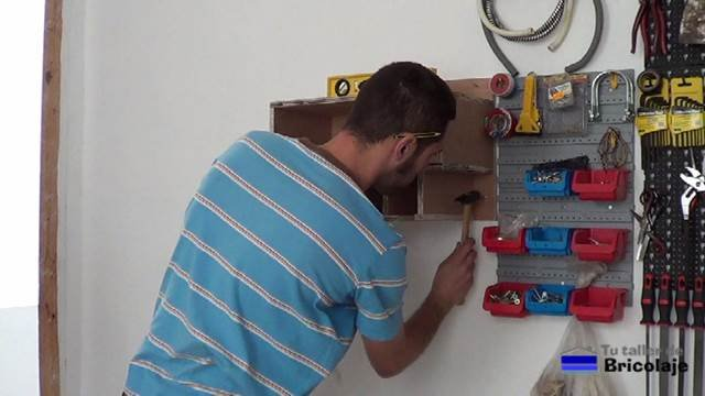 marcando en la pared el lugar donde colocar el mueble organizador de taladros y sus accesorios