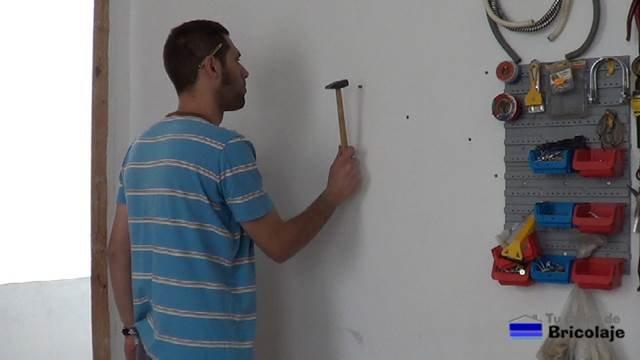 insertando los tacos en la pared para sujetar el mueble organizador de taladros