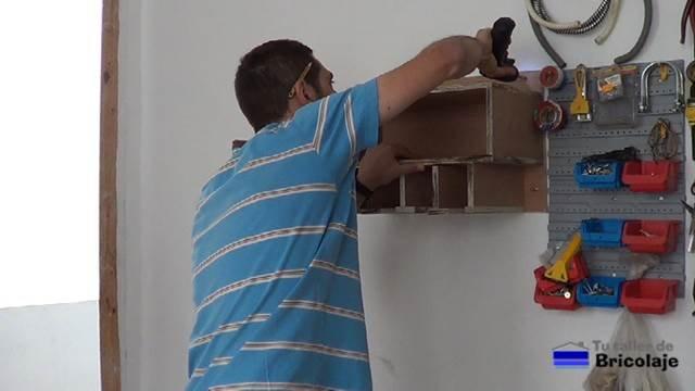 atornillando el mueble organizador de taladros y sus accesorios a la pared