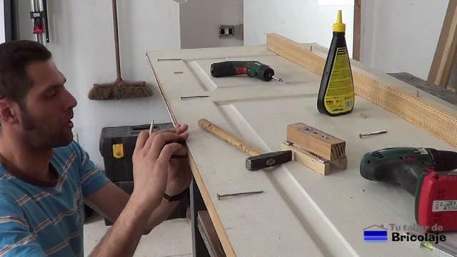 marcando el lugar donde colocar los tarugos, espigas o tubillones en el lado de la puerta
