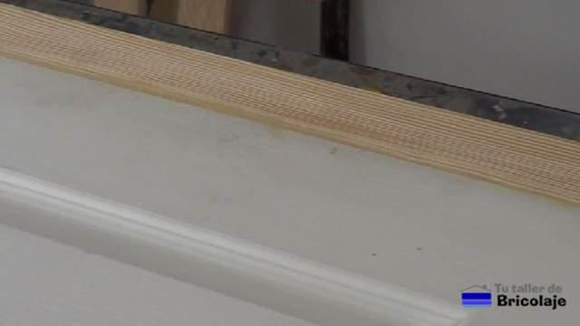 después de aplicar la masilla entre la unión de la puerta prefabricada y el listón de madera para aumentar el ancho a la misma