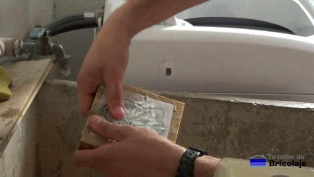 retirando el papel con el dedo depués de mojarlo con agua
