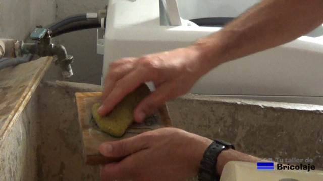 mojando la madera con una esponja