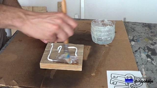 extendiendo el gel medio sobre la madera para transferir la imagen a la madera