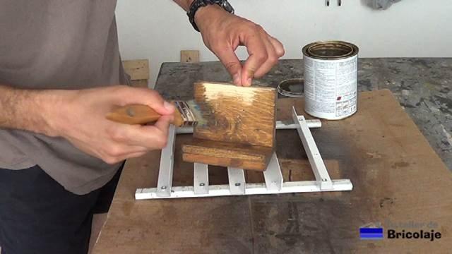aplicando el barniz tinte al soporte de madera para tableta o tablet